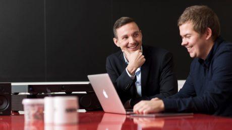 Kaksi liikemiestä työskentelemässä kannettavan tietokoneen ääressä.