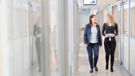 Kaksi naista kävelemässä hyvin valaistua toimiston käytävää pitkin.