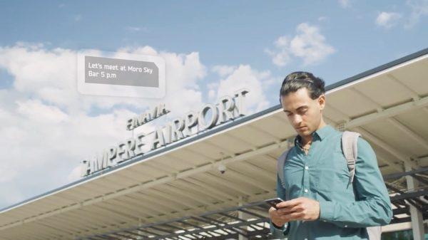Kuva miehestä lukemassa viestiä puhelimestaan Pirkkalan lentokentällä.