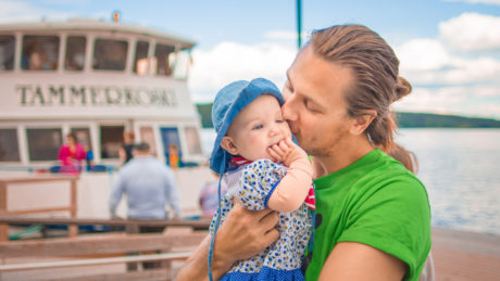 Talent Tampere - Happy father holding a baby on Viikinsaari island with Hopealinjat ferry behind them, by Laura Vanzo