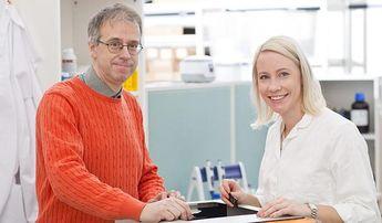 Mies ja nainen pöydän ääressä hymyilemässä kameraan ammattimaisessa ympäristössä