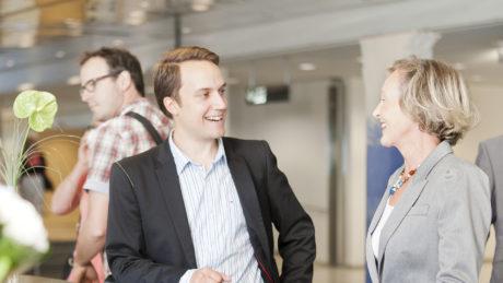 Mies ja nainen keskustelevat sijoittumisesta ja investoinneista Tampere-talossa.