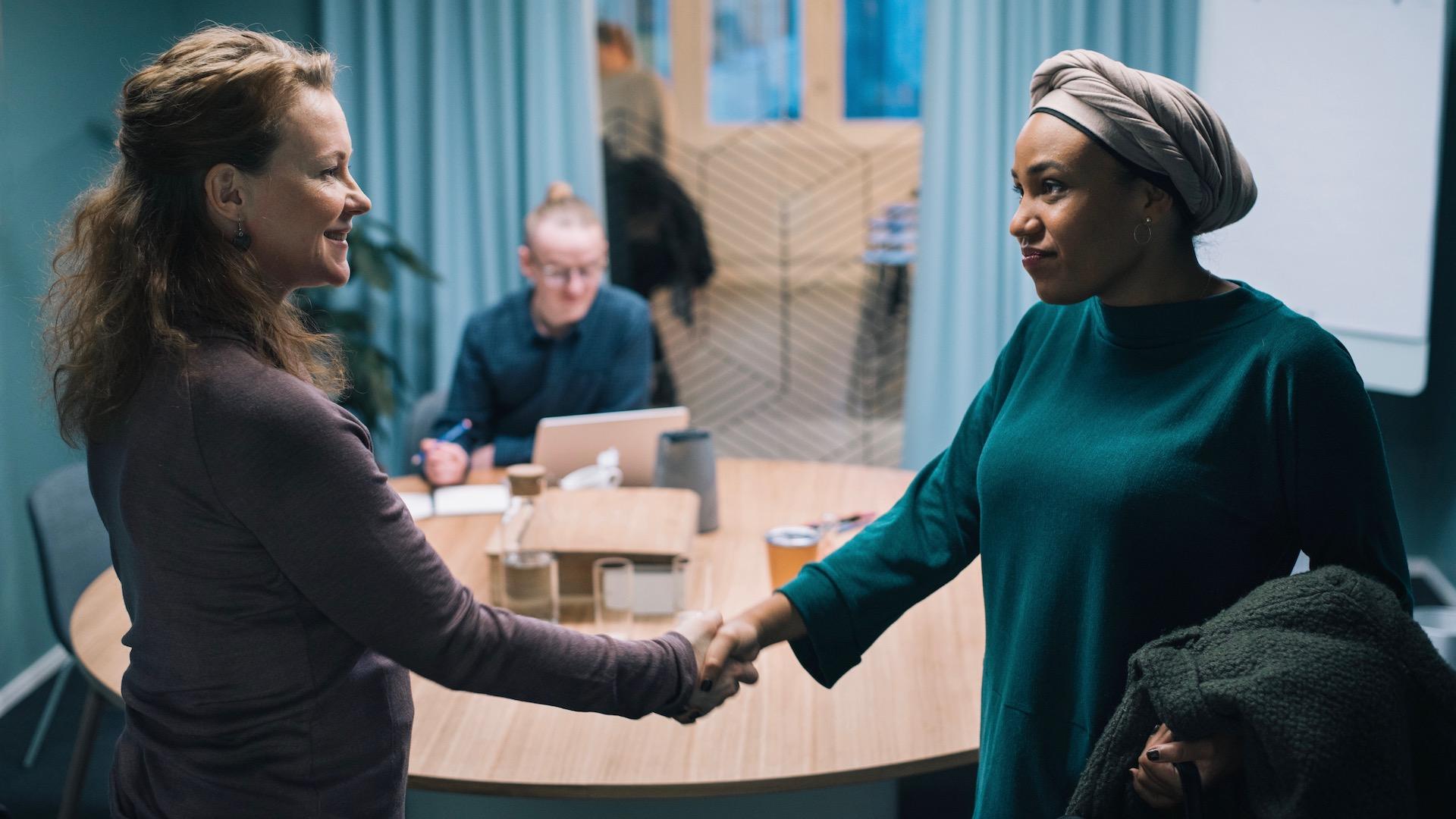 Kohtaus elokuvasta, kaksi naista kättelee