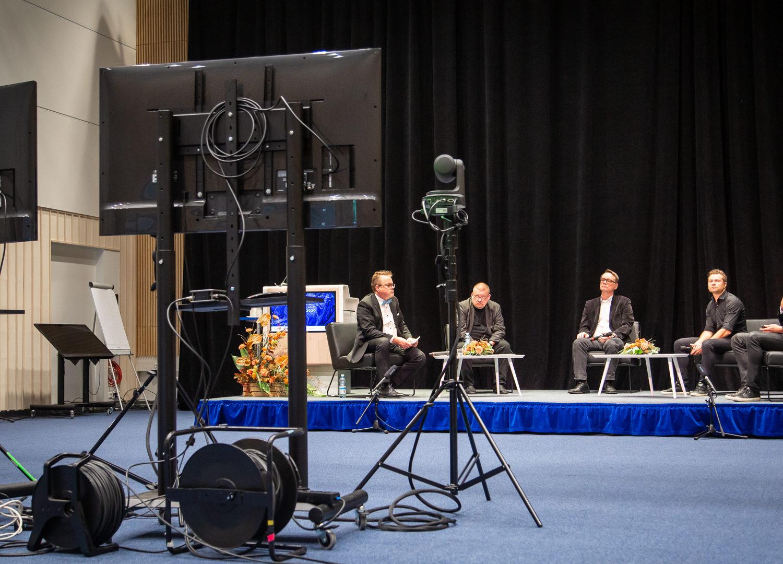 Paneelikeskustelu AI Finland -tapahtumassa. Viisi miestä istuu tuoleilla.